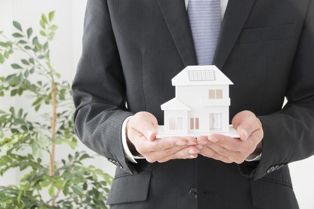 家の模型を見せるビジネスマン