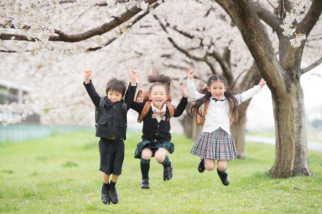 入学式でジャンプして喜ぶ3人の小学生