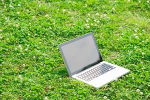 芝生上のノートパソコン