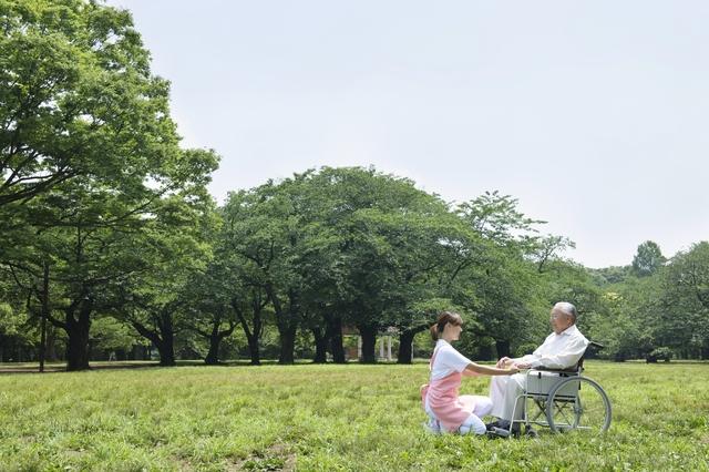 公園で車いすの患者さんと介護士さん