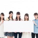 横断幕で宣伝する5人の女の子