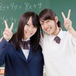 黒板の前でピースサインする2人の女子高校生